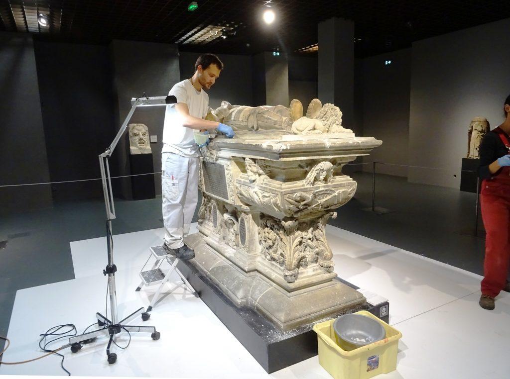 Adrien Gaillard, conservateur-restaurateur pratiquant des tests de nettoyage sur le gisant de Montaigne